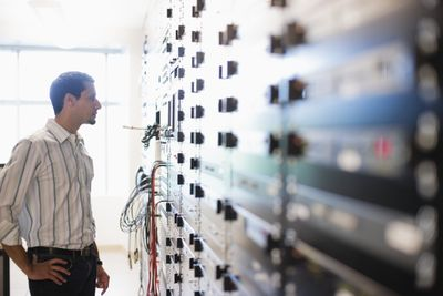 Network technician looking at a wall of servers