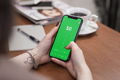 A person using Cash App on an iPhone X.