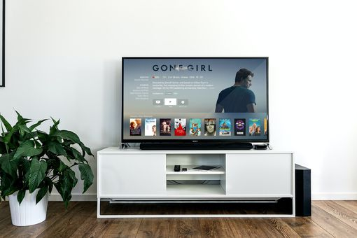 Netflix displayed on a TV sitting on a white TV stand against a white wall and wood floors.