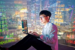 Asian man in glasses with a laptop, trading cryptocurrencies