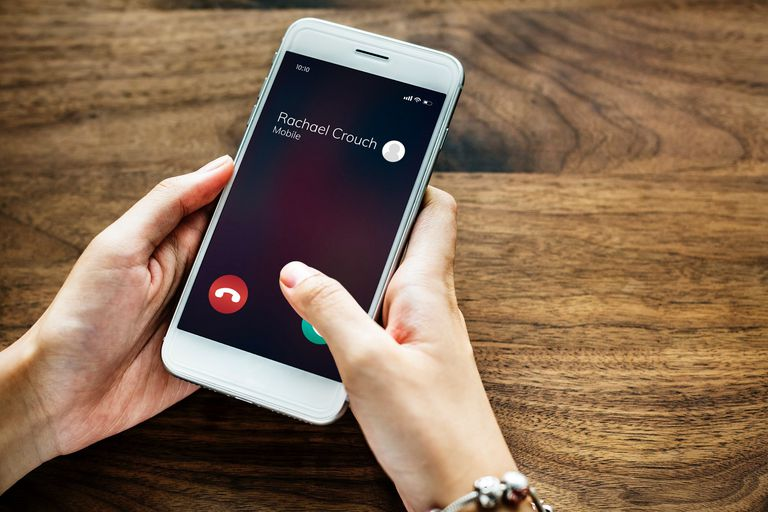 """Photo of someone holding a smartphone with an """"incoming phone call"""" screen."""