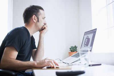Man working on graphic design project on laptop in home office.