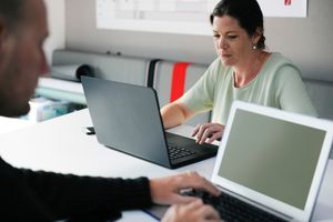 Man and woman working remotely on laptop computers
