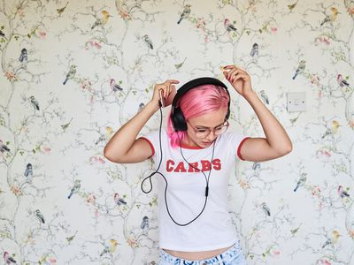 Enthusiastic young woman with pink hair listening to music at home