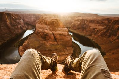 Legs and feet hanging off edge of cliff in front of Grand Canyon