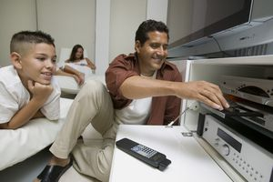Father and son using DVD player