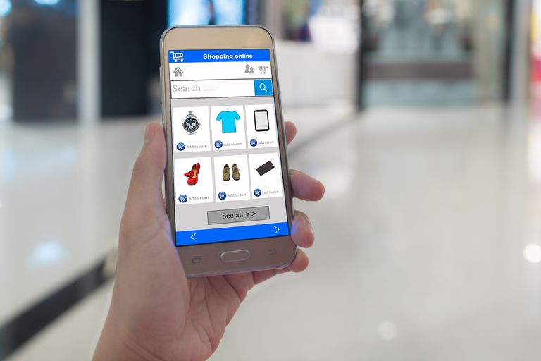 An image of a person holding up a smartphone while shopping online.