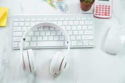 A close up of a Mac keyboard with a pair of headphones on top of it and a mouse next to it