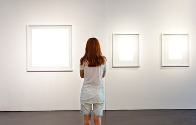 A woman looking at missing photos in a gallery.