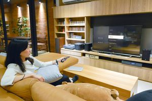 A woman sitting on a lounge while pointing a remote control at her TV which is showing an Amazon Fire TV Stick with a USB stick connected.