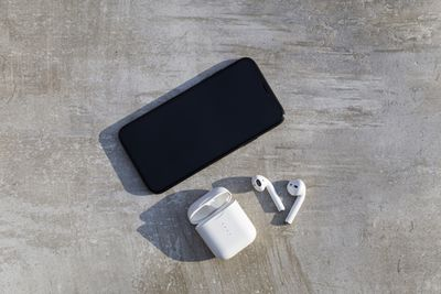 An iPhone and AirPods resting on a piece of wood