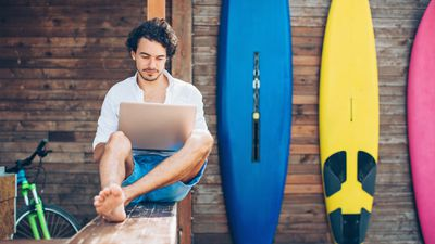 A man on a Windows 10 laptop next to colorful surfboards.