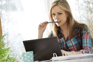Woman biting pen looking at laptop