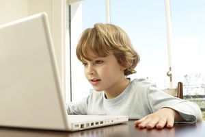Boy (4-5) using laptop at home