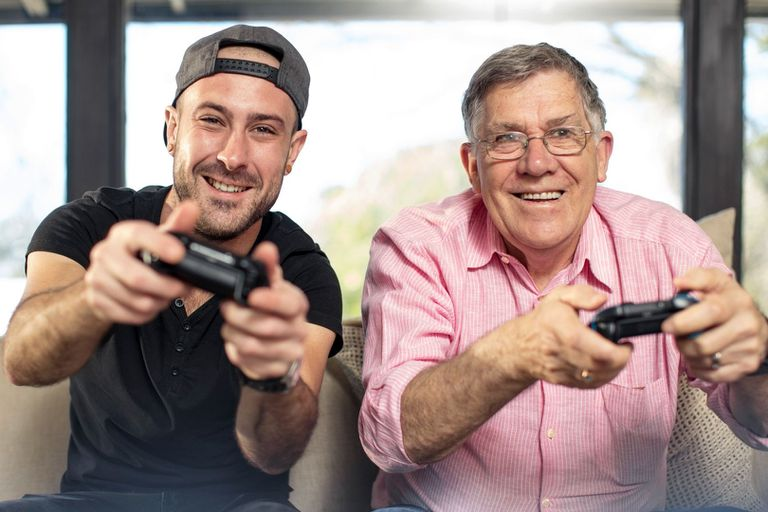 A young man and an old man playing video games on an Xbox One console.