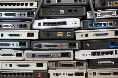 A stack of old Wi-Fi routers, wired routers, and modems