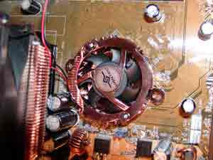 A CPU cooling fan aligned over the mounting holes of a motherboard.