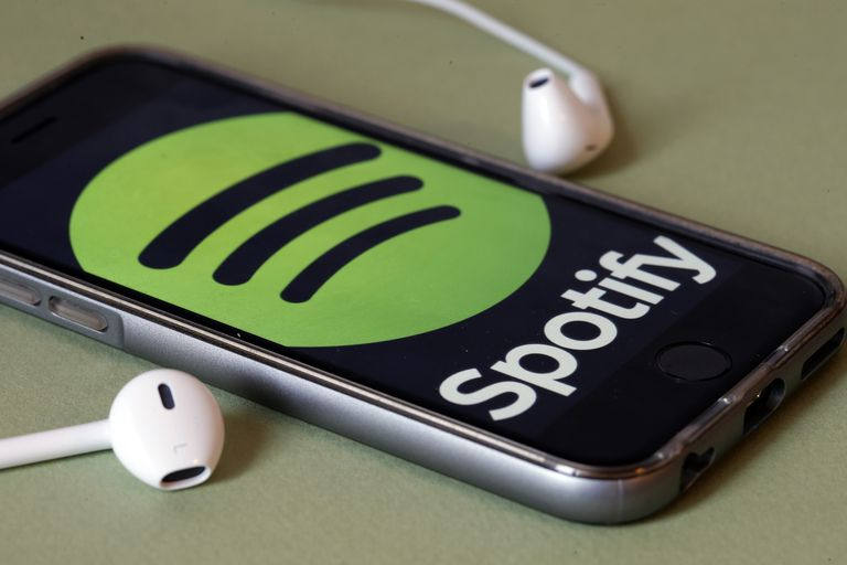 Spotify logo on smartphone with earbuds