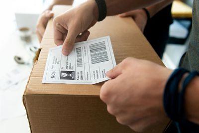 A man sticking his own barcode sticker onto a box