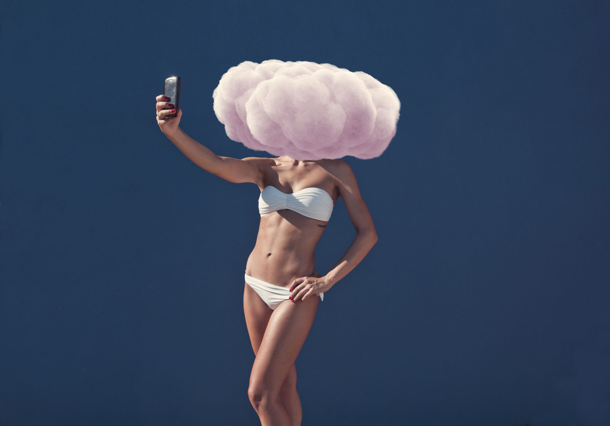 A woman taking a selfie with a pink cloud in front of her head