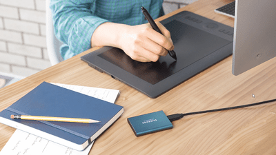 Samsung T5 sitting on a table next to a drawing tablet