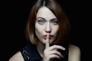 Brunette woman with blue eyes shushing the camera