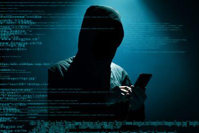 Hacker using phone in the dark