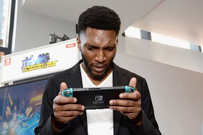 Man plays the Nintendo Switch in handheld mode.