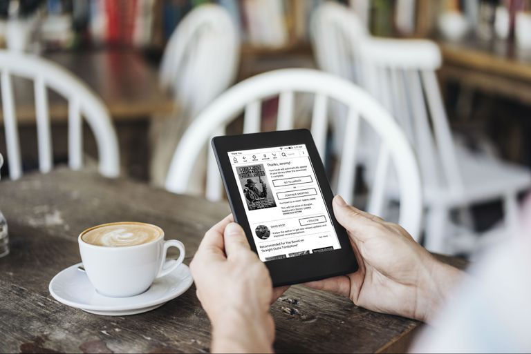 A man using a Kindle in a coffee shop.