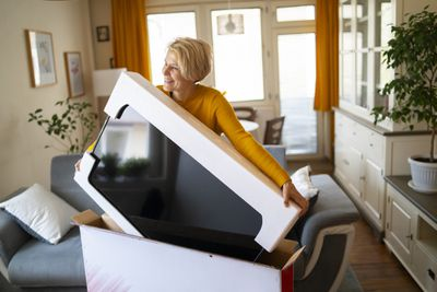 new television out of the box with woman carrying tv