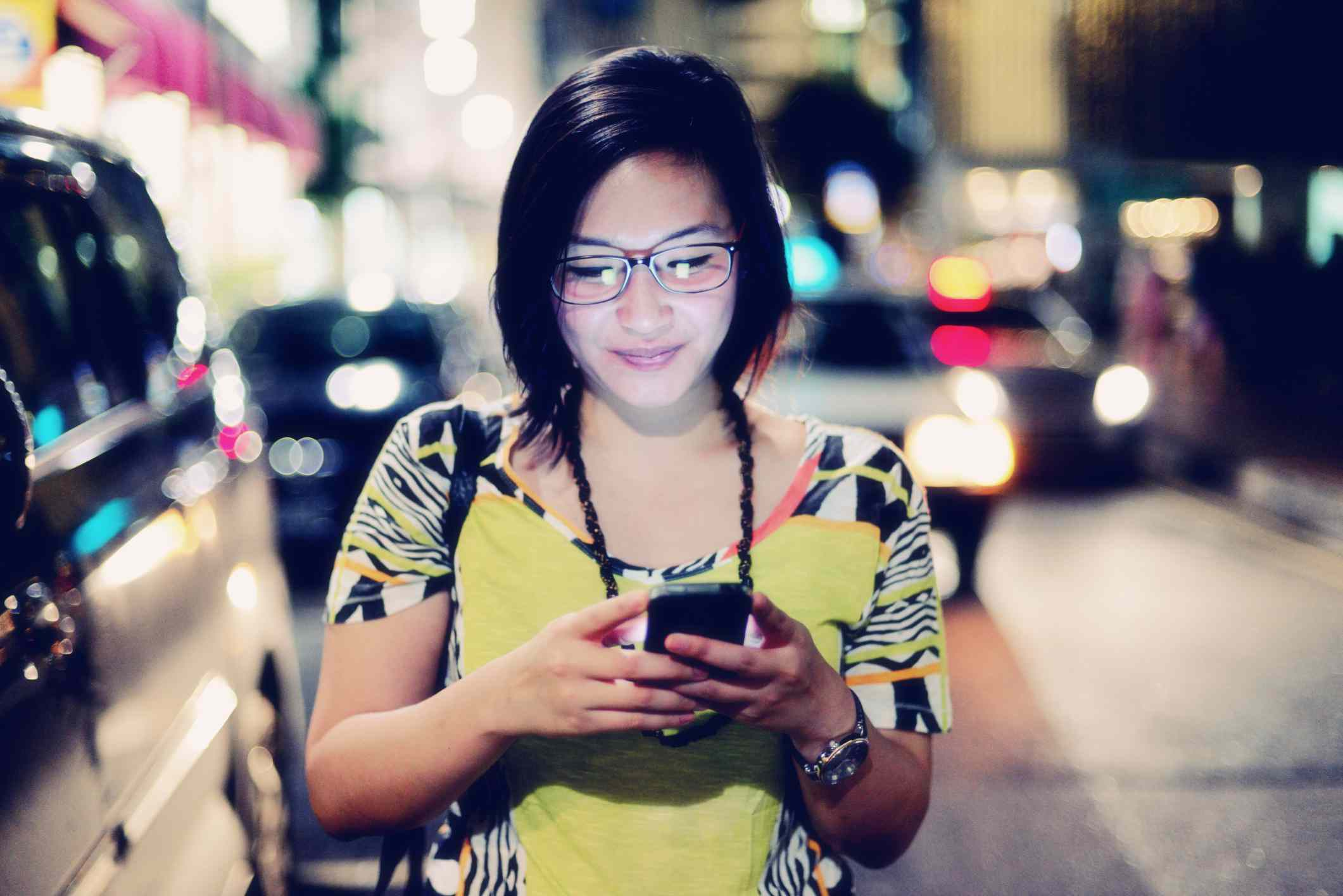 Pedestrian types on a smartphone on a city street at night