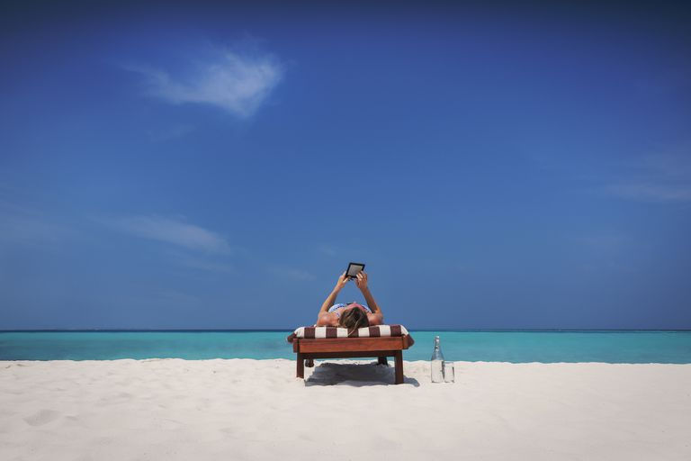 Woman relaxing, sunbathing, laying on lounge chair and using digital tablet on sunny tropical beach