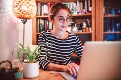 Young Asian woman working on a laptop computer at home