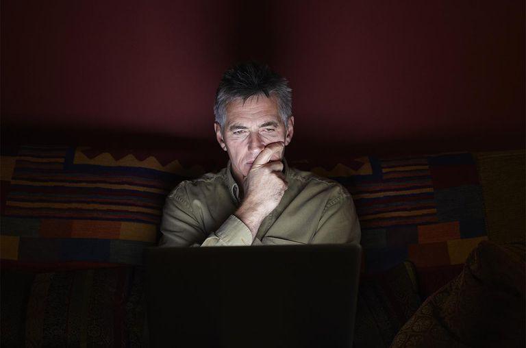 Man sat on sofa using laptop at night