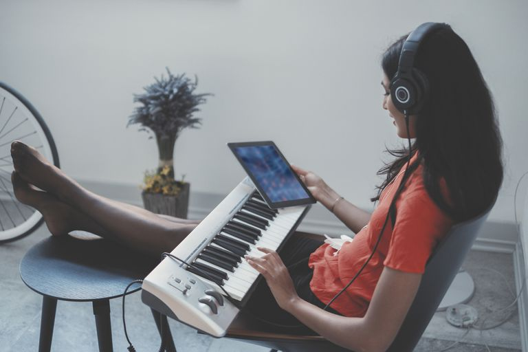 Young woman with digital keyboard using iPad to create music