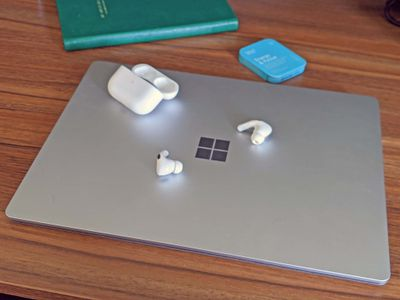AirPods and an AirPod case resting on a Windows 11 PC laptop.