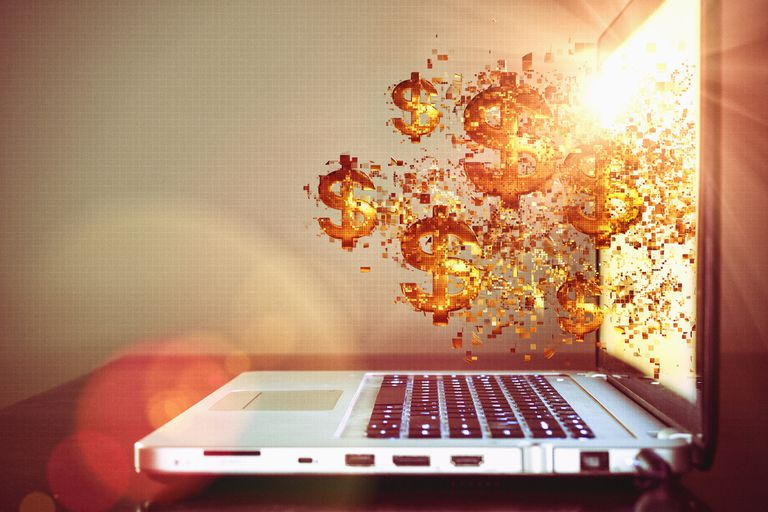 Cryptocurrency - gold dollar signs coming out of laptop screen.
