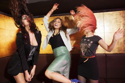 Three women dancing and flipping their hair