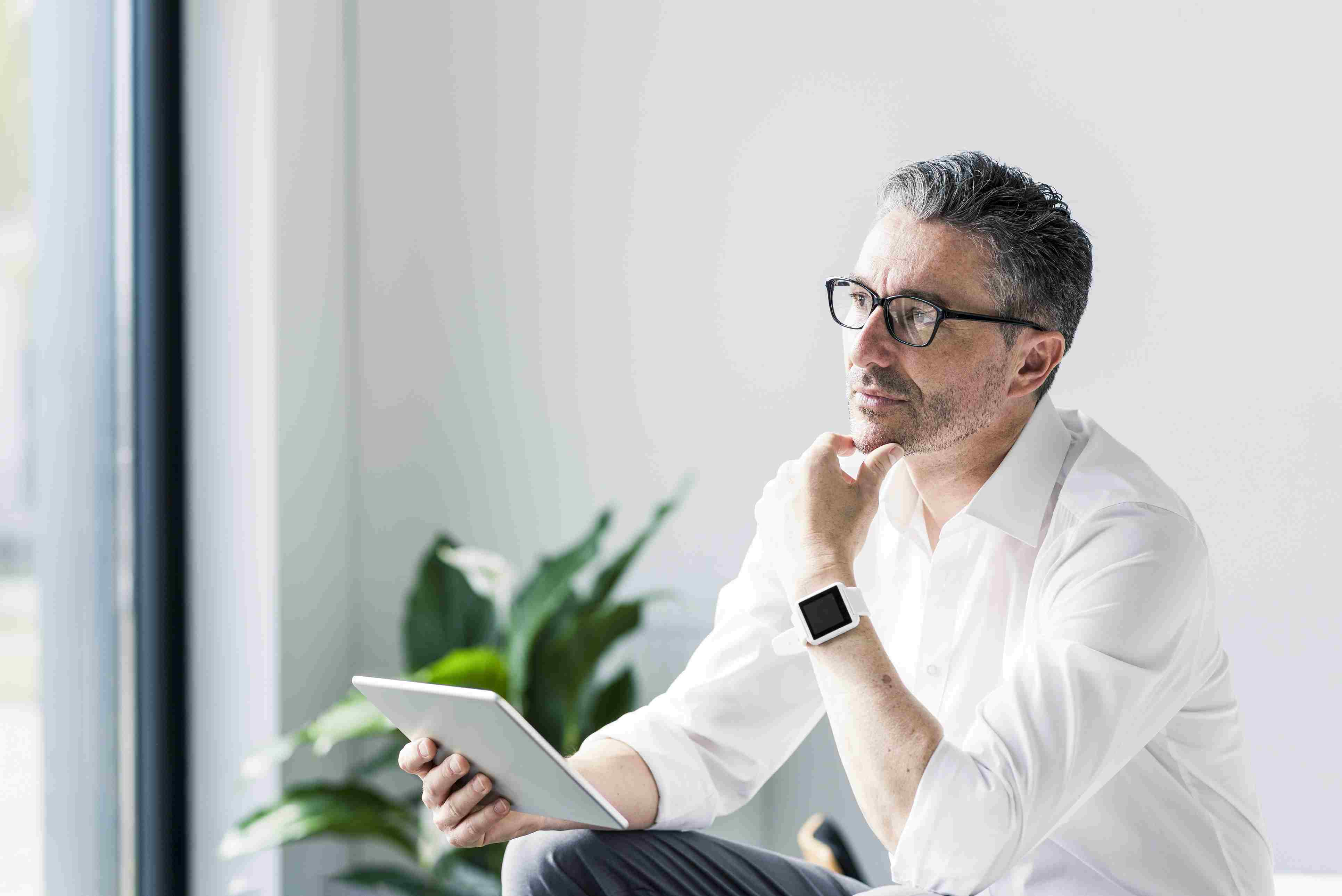 Portrait of pensive businessman with tablet and smartwatch.