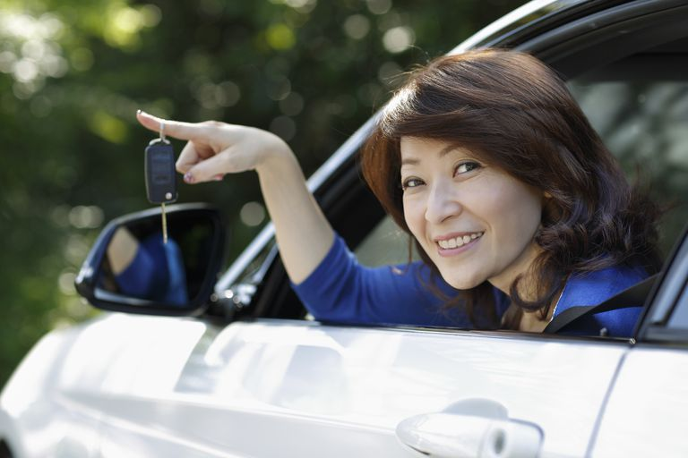 Woman dangling keys to her new EV.