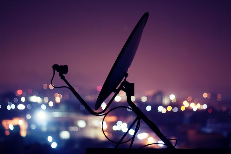Dish antenna at night with bulbs glowing in background resembling population.