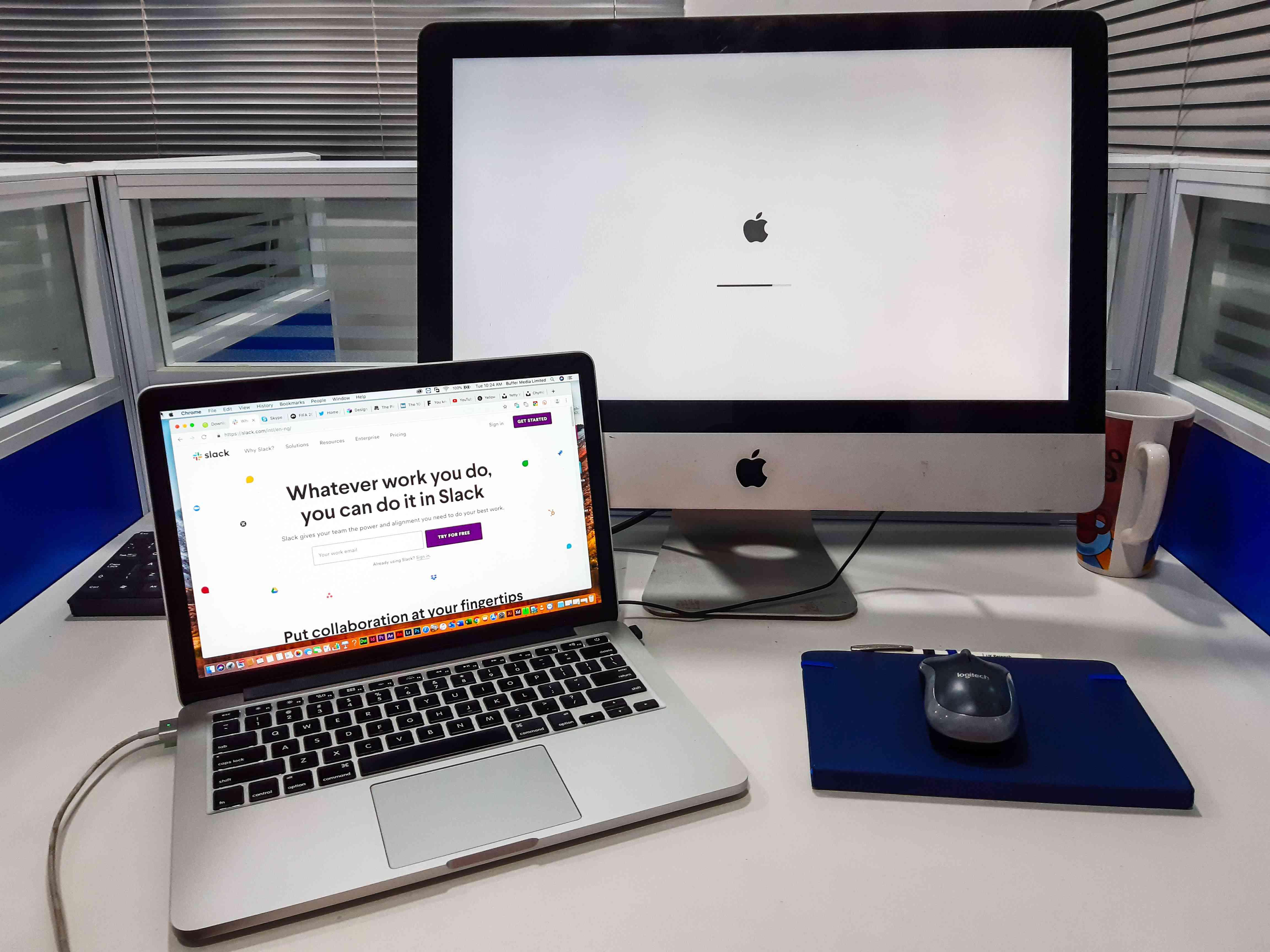 A mac computer with an iMac behind it going through an update.