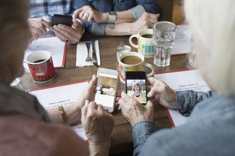 Several older people share photos on their phones while sitting at a table