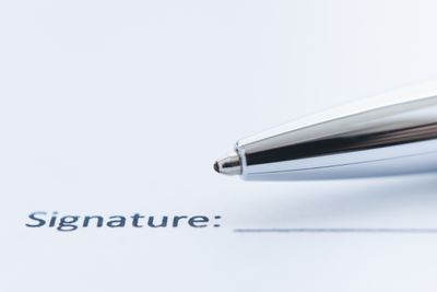 Image of a pen tip next to a signature line on paper