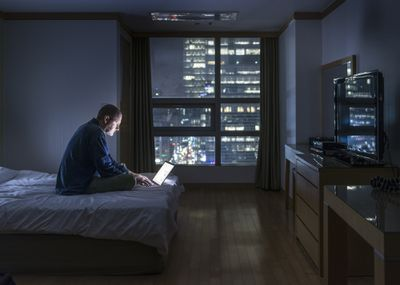 Man looking at computer in bed