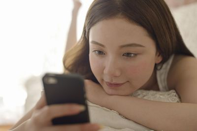 Child using a smartphone while on a sofa