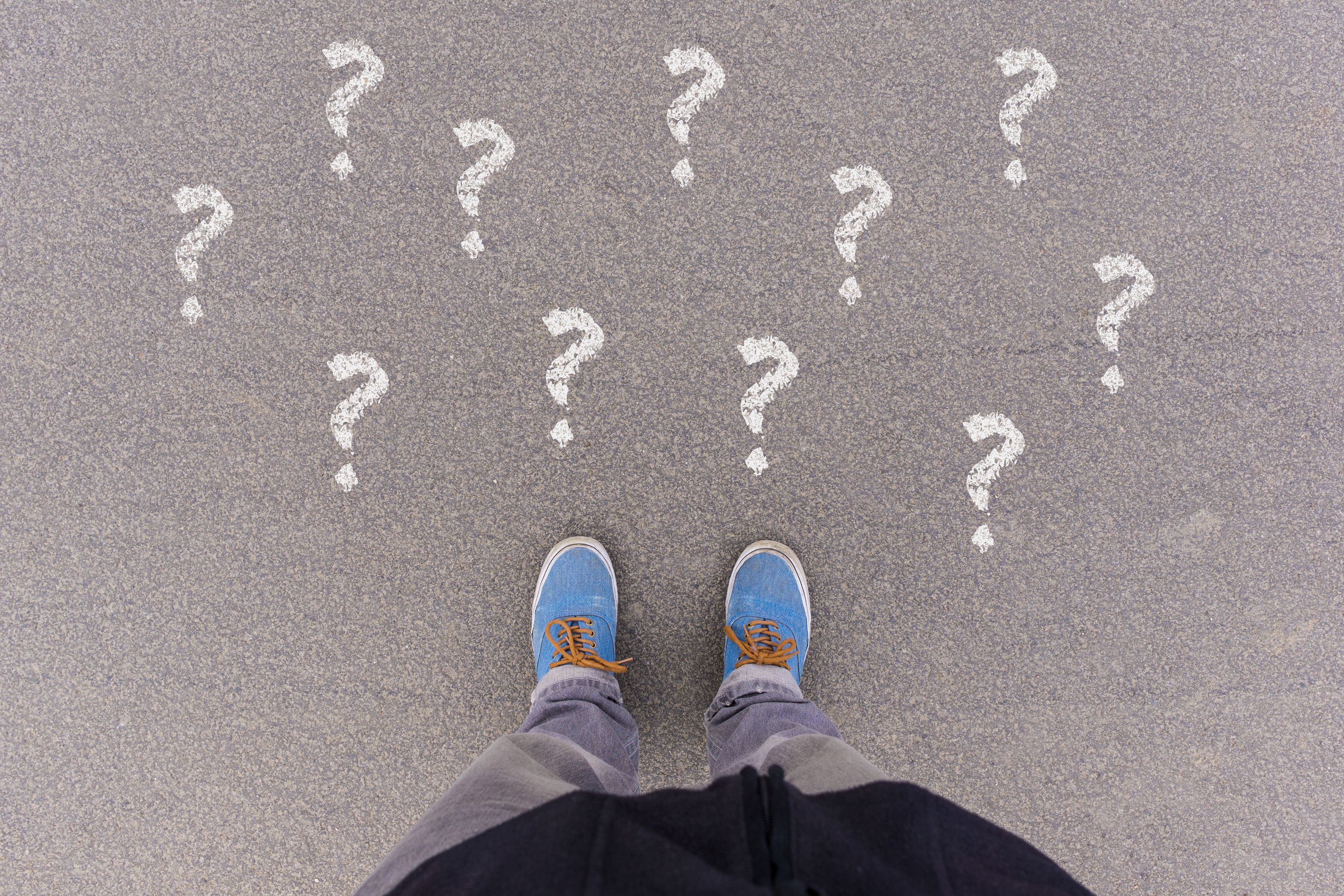 A picture of a pair of shoes on pavement with question marks around them.