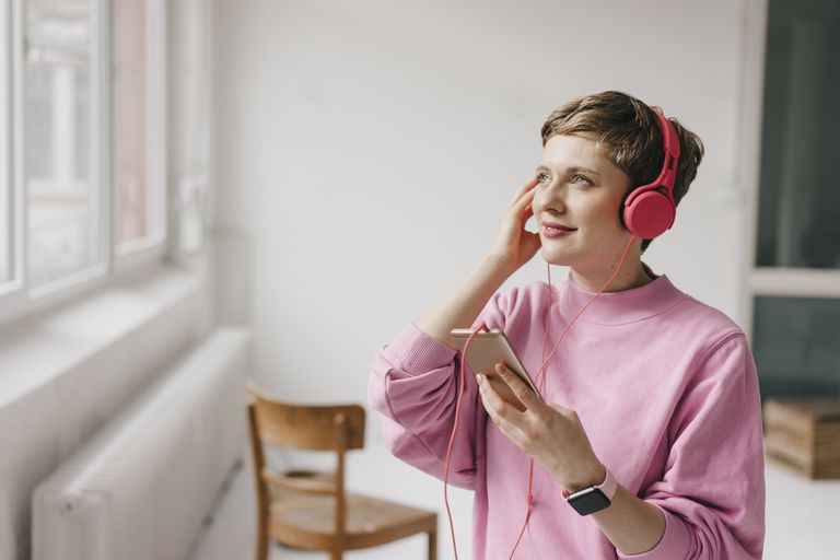 Woman smiling with headphones and a cell phone, listening to music