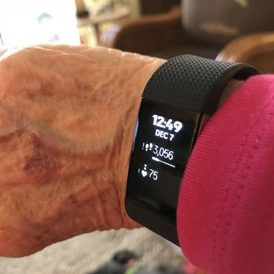 Someone wearing a Fitbit device showing a steps count.