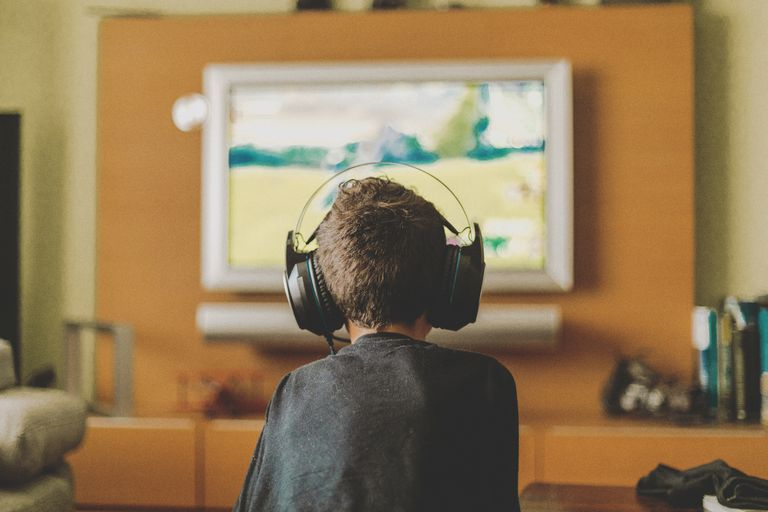 A boy wearing headphones playing a console game on a TV